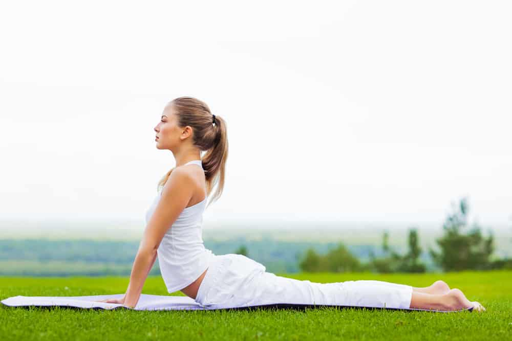 Getting In Shape Woman Outdoor on a mat doing yoga