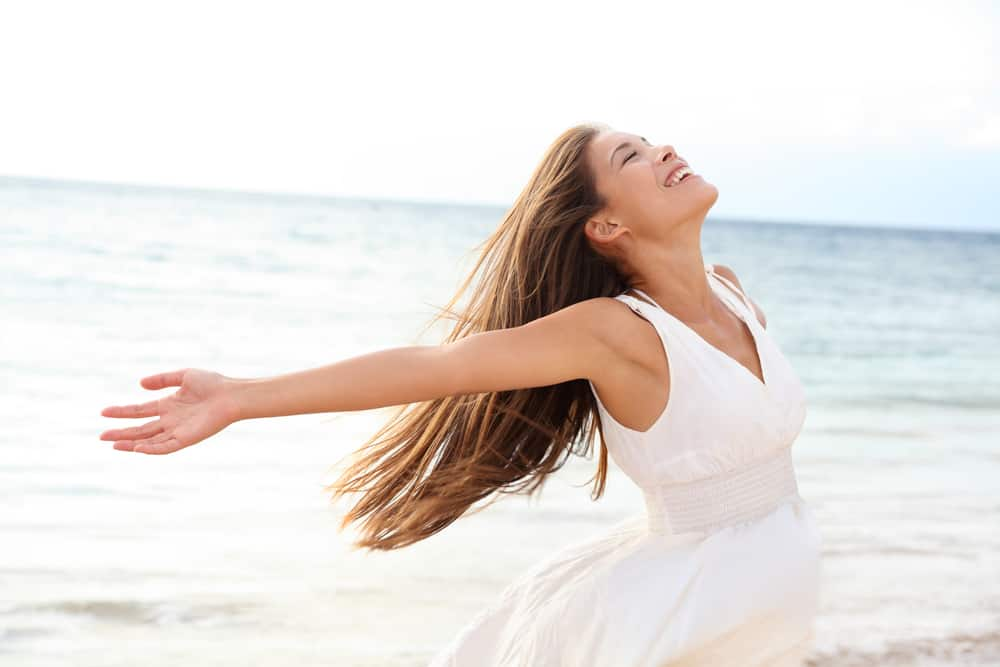 Embrace Change Woman relaxing at beach enjoying summer freedom with open arms and hair in the wind by the water seaside. Mixed race Asian Caucasian girl on summer travel holidays vacation outside.