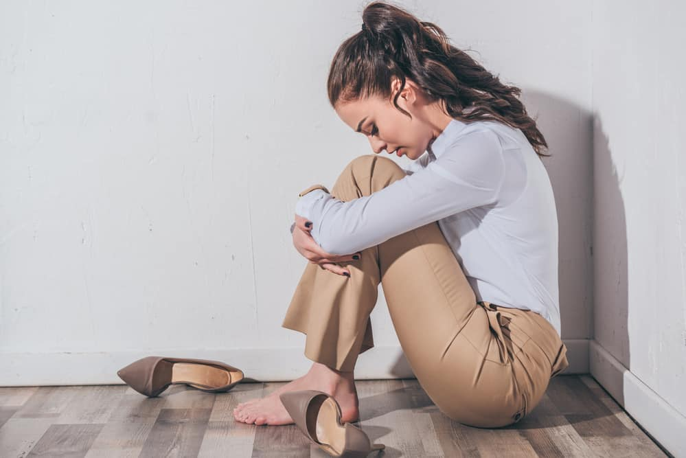 Self-Doubt Sad woman in white blouse and beige pants sitting on floor with head bent near white wall at home