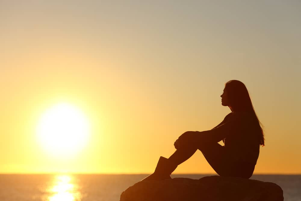 Journal Prompts For Self-Discovery Woman silhouette watching sun in a sunset